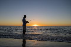 Silhouette of fisherman with hat on the beach with fish rod standing on sea water fishing at sunset with beautiful orange sky in v Stock Image