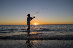 Silhouette of fisherman with hat on the beach with fish rod standing on sea water fishing at sunset with beautiful orange sky in v Stock Photo
