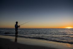 Silhouette of fisherman with hat on the beach with fish rod standing on sea water fishing at sunset with beautiful orange sky in v Royalty Free Stock Images