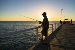 Silhouette of fisherman with hat and fish rod standing on sea dock fishing at sunset with beautiful orange sky in vacations relax royalty free stock photo