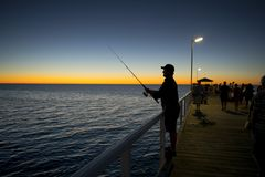 Silhouette of fisherman with hat and fish rod standing on sea dock fishing at sunset with beautiful orange sky in vacations relax. Hobby and leisure holidays Stock Photography