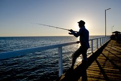 Silhouette of fisherman with hat and fish rod standing on sea dock fishing at sunset with beautiful orange sky in vacations relax stock images