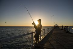Silhouette of fisherman with hat and fish rod standing on sea dock fishing at sunset with beautiful orange sky in vacations relax. Hobby and leisure holidays Royalty Free Stock Photos
