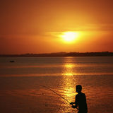 Silhouette of a fisherman and his fishing rod during sunset Stock Image