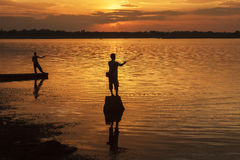 Silhouette fisherman of Lake in action. Stock Images