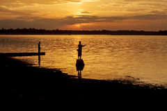 Silhouette fisherman of Lake in action when fishing. Stock Photos