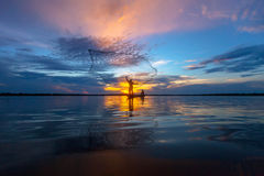 Silhouette fisherman with net at the lake