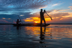 Silhouette fisherman with net at the lake Royalty Free Stock Photo