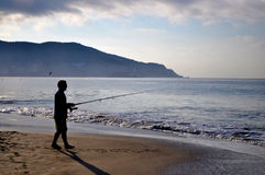 Silhouette of fisherman on the Pacific ocean coastline. Silhouette of fisherman casting a line and fishing on the Pacific ocean coastline. Man fishing with Stock Images