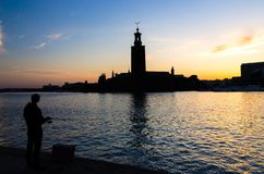 Silhouette of fisherman with pole and Stockholm City Hall, Swede stock photo