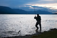Silhouette of a fisherman pulling a fish Stock Images