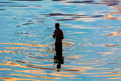 Silhouette of a fisherman in reflection in water ripples Stock Photos