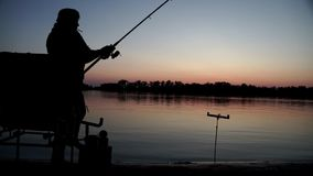 Silhouette fisherman on river bank waiting for bite on fishing rod. On background evening sunset. Beautiful landscape evening sunset during fishing on river stock footage