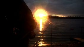 Silhouette fisherman on river nearly fishing rod on evening sunset. Silhouette fisherman sitting on chair by river nearly fishing rod waiting for bite on stock video
