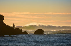 Silhouette of fisherman on rocks with waves breaking Royalty Free Stock Photos