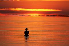Silhouette of a fisherman in the sea Royalty Free Stock Photo