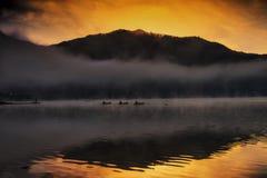 Silhouette fisherman at Shoji lake during sunrise. Silhouette fisherman on shore and boats fishing at lake Shoji during sunrise with heavy mist and reflection on Royalty Free Stock Photo