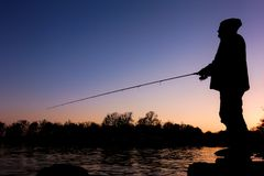 Silhouette of a fisherman. Silhoutte of a sportsfisheman standing on a rock and fishing on a bay in Blekinge Sweden at sunset time Stock Photography