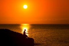 Silhouette of fisherman sitting with rod on the sunset Stock Photo