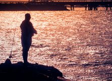 Silhouette of fisherman with sparkling sea water reflected Royalty Free Stock Photos