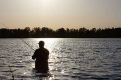 Fisherman. Silhouette of fisherman standing in the lake and catching the fish during sunny day Royalty Free Stock Images