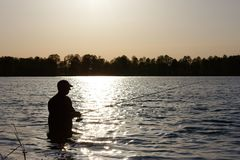 Fisherman. Silhouette of fisherman standing in the lake and catching the fish during sunny day Stock Photos