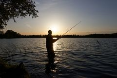 Fisherman. Silhouette of fisherman standing in the lake and catching the fish during sunset Royalty Free Stock Photography