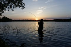 Fisherman. Silhouette of fisherman standing in the lake and catching the fish during sunset Stock Photos