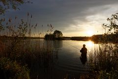 Fisherman. Silhouette of fisherman standing in the lake and catching the fish during sunset Royalty Free Stock Image