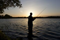 Fisherman. Silhouette of fisherman standing in the lake and catching the fish during sunset Stock Photography