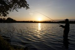 Fisherman. Silhouette of fisherman standing in the lake and catching the fish during sunset Royalty Free Stock Photos