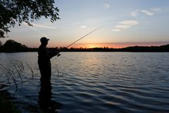 Fisherman. Silhouette of fisherman standing in the lake and catching the fish during sunset Stock Images