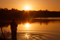 Fisherman. Silhouette of a fisherman during sunrise on lake stock photos