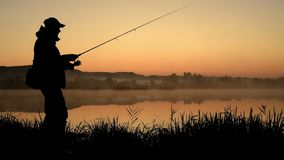 Silhouette of Fisherman. At sunrise. Fisherman On Morning Fishing.  at sunset. sport hobby fishing. Morning fishing at the dawn stock video footage