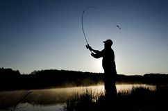 Silhouette of a fisherman at sunrise with a rod royalty free stock photos