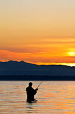 Silhouette of a fisherman at sunset. Stock Image