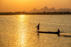 A silhouette fisherman throw a net to catch a fish in a river in Stock Photo