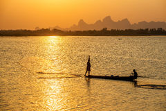 A silhouette fisherman throw a net to catch a fish in a river in Royalty Free Stock Photos