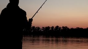 Silhouette fisherman throwing fishing rod in river on background evening sunset. Back view. Beautiful evening sunset during fishing on river stock footage
