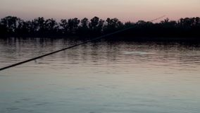 Silhouette fisherman throwing fishing rod in river on background evening sunset. Beautiful evening sunset during fishing on river stock video footage