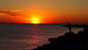 Silhouette of fisherman throws fishing-rod stock video footage