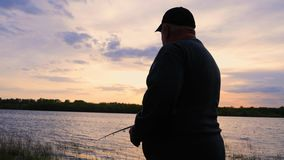 Silhouette fisherman throws a fishing tackle in the river at dawn. Silhouette fisherman throws a fishing tackle in the river at dawn stock footage