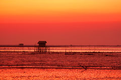 Silhouette of fisherman village on sunset Stock Photos