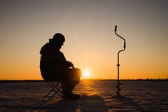 Silhouette of a fisherman on winter ice fishing at sunset.