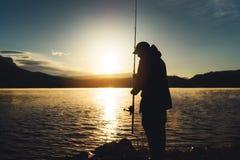 Silhouette fisherman wirh fishing rod at sunrise sunlight, outline man enjoy hobby sport on evening lake, person catch fish