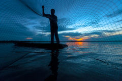 Silhouette of fisherman in wooden boat Royalty Free Stock Images