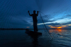 Silhouette of fisherman in wooden boat Royalty Free Stock Photos