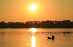 Silhouette of a fisherman working on his boat at the lake before sunset. Nature Background stock images