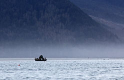 Silhouette Of Fishermen In Boat On Bay In Mist Royalty Free Stock Images