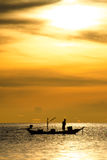 Silhouette of fishermen in the boat on sea with yellow and orange sun in the background Royalty Free Stock Photography